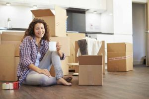Woman Moving Into New Home And Unpacking Boxes Sitting On Floor