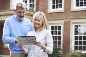 Mature Couple Standing Outside House